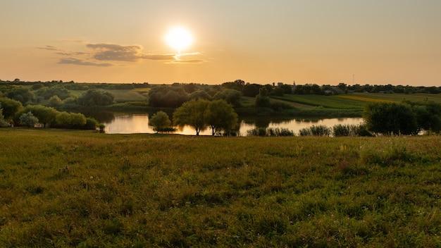 Magnifico scenario tramonto sui campi del lago, burroni e alberi cielo nuvoloso ed erba verde brillante