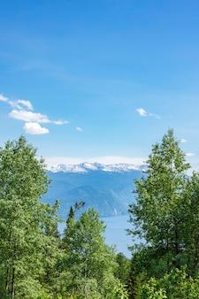 Magnifiche montagne innevate di altai nella foschia blu sul lago teletskoye con una copia dello spazio