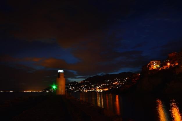 Magnifica veduta del faro di camogli luci e colori si riflettono sul mare creando un