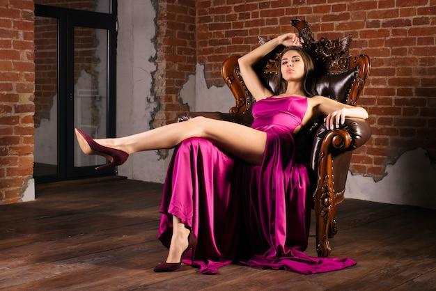 Magnifica giovane donna in abito lussuoso è seduta su una sedia in un appartamento di lusso. interni classici vintage. bellezza, moda.