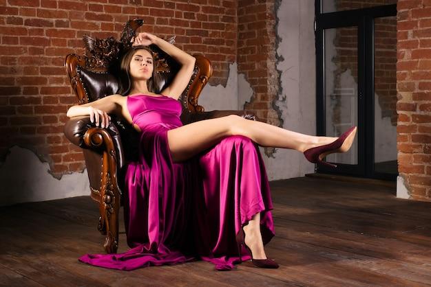 Magnifica giovane donna in abito lussuoso è seduta su una sedia in un appartamento di lusso