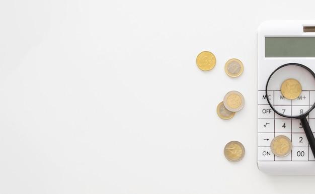Lente di ingrandimento sulla calcolatrice con copia spazio e monete