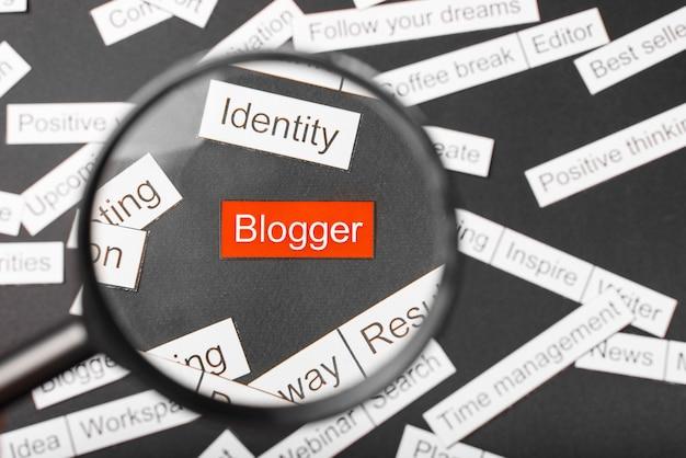 Lente di ingrandimento sopra l'iscrizione rossa blogger ritagliata di carta. circondato da altre iscrizioni