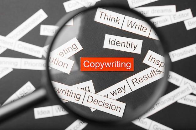 Lente d'ingrandimento sopra la scritta rossa copywriting ritagliata di carta. circondato da altre iscrizioni su uno sfondo scuro. concetto della nuvola di parola.