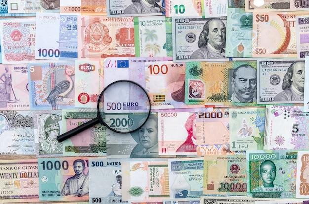 Lente di ingrandimento su sfondo di banconote di denaro internazionale, primi piani