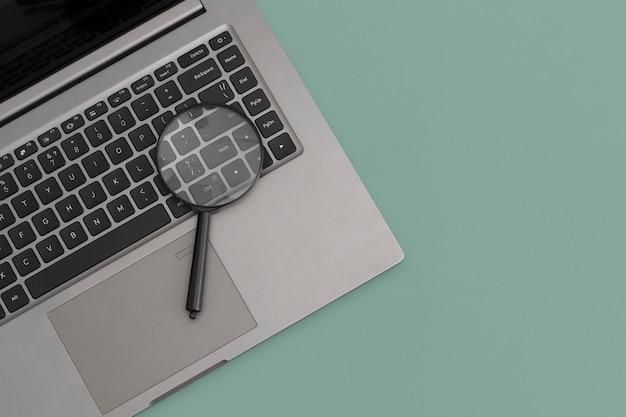 Lente d'ingrandimento sul computer portatile su sfondo verde. concetto di business, strategia