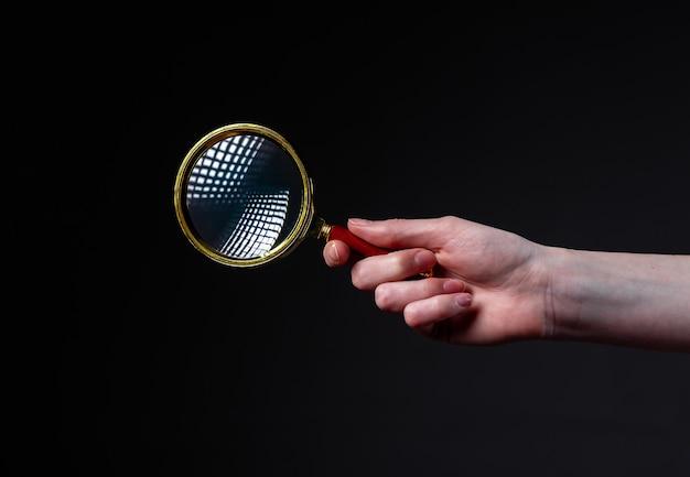 Lente di ingrandimento o lente di ingrandimento in mano della donna su sfondo nero. concetto di ricerca e studio.