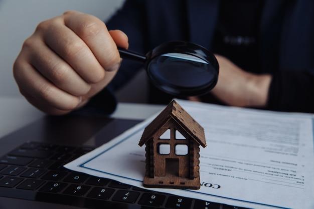 Lente d'ingrandimento, mano d'uomo e casa. concetto di affitto, ricerca, acquisto di immobili