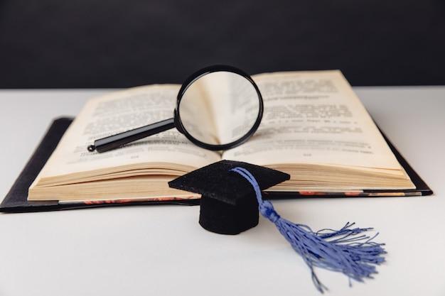 Lente d'ingrandimento sul libro aperto e berretto di laurea sul tavolo bianco. concetto di educazione.