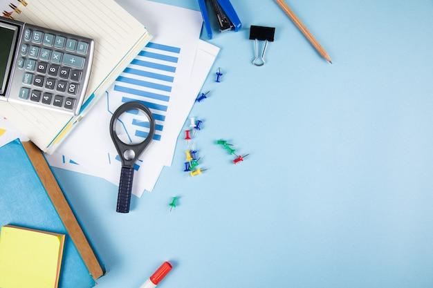 Lente d'ingrandimento, statistiche e calcolatrice sul tavolo blu