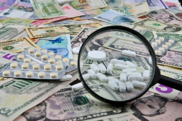 Lente d'ingrandimento, compresse e termometro su banconote di paesi diversi. la disponibilità medica e l'aumento delle spese mediche.