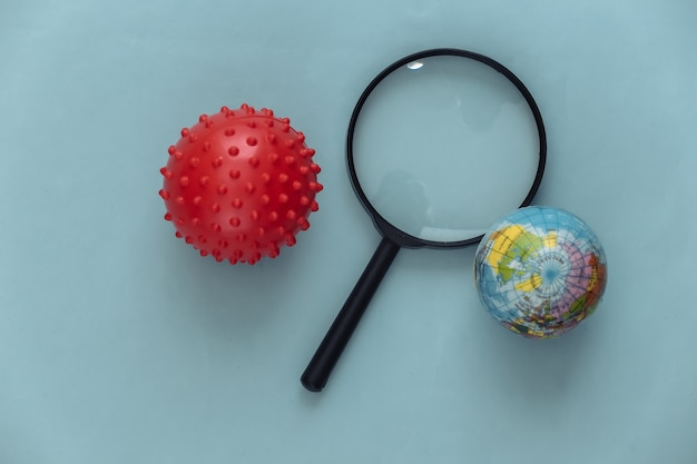 Lente d'ingrandimento con un modello di un ceppo del virus, globo su un blu