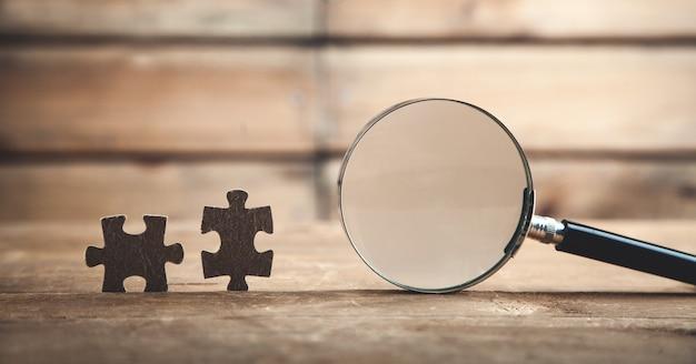 Lente d'ingrandimento con puzzle. concetto di affari