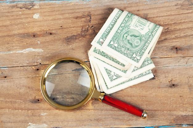 Una lente d'ingrandimento e una banconota sul tavolo