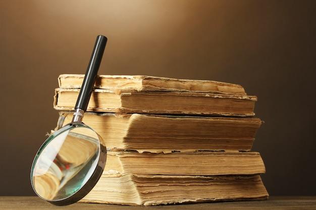 Lente d'ingrandimento e libri su colore marrone