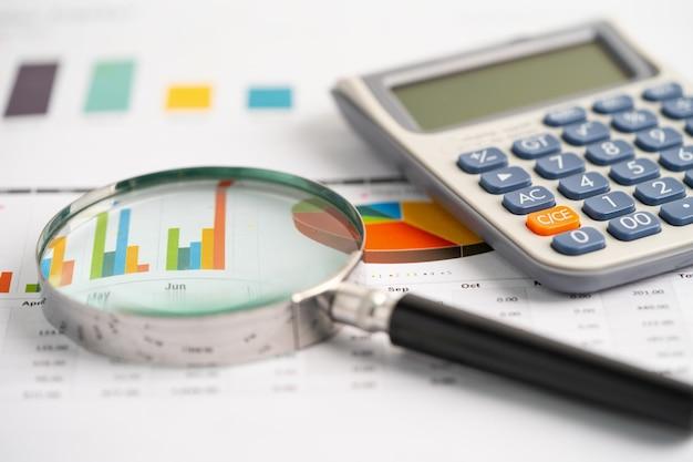 Lente d'ingrandimento e calcolatrice su carta millimetrata. sviluppo finanziario, conto bancario, statistiche, economia dei dati di ricerca analitica degli investimenti, negoziazione in borsa, concetto di ufficio commerciale.