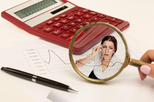 Lente d'ingrandimento sul grafico su carta, calcolatrice, penna - affari, banche, concetto di finanza. collage