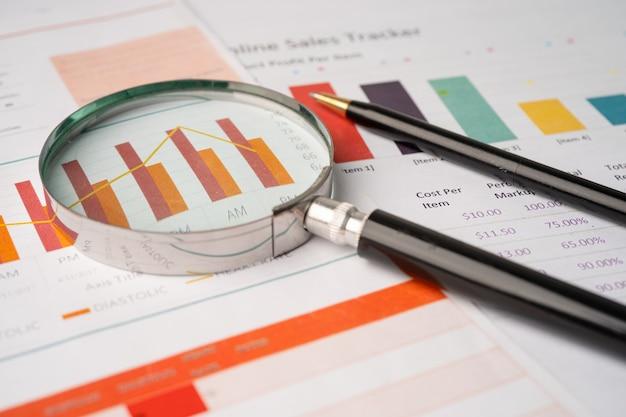 Lente d'ingrandimento sulla carta dei grafici dei grafici. sviluppo finanziario, conto bancario, statistiche, economia dei dati di ricerca analitica degli investimenti, commercio di borsa, concetto di riunione della società dell'ufficio commerciale.