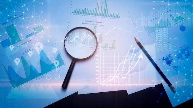 Lente d'ingrandimento e documenti con dati analitici distesi sul tavolo