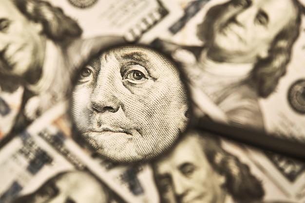 Lente d'ingrandimento su sfondo di fatture di dollari. banconote da cento dollari usd. problemi economici e finanziari