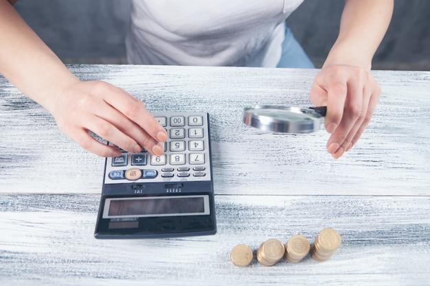 Una lente d'ingrandimento esamina i soldi e calcola su una calcolatrice