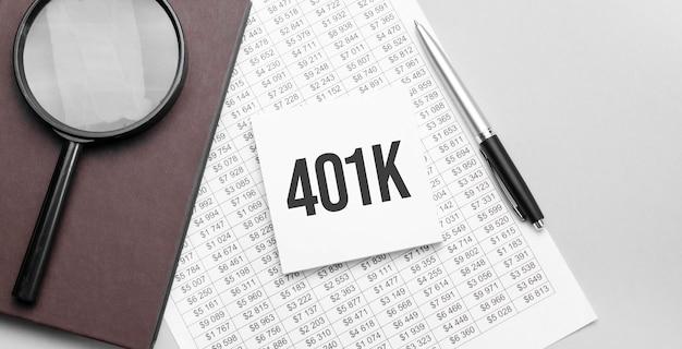 Lente d'ingrandimento, documento finanziario, foglio di carta bianco con segno 401k e taccuino marrone su sfondo grigio.