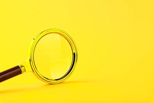 Lente d'ingrandimento in una cornice d'oro su un giallo