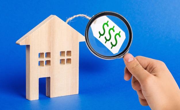 Una lente d'ingrandimento guarda una figura di casa in legno e un prezzo da pagare. vendere una casa o un'asta.