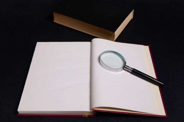 Una lente d'ingrandimento, una lente d'ingrandimento, una lente d'ingrandimento su un libro aperto con copertina rigida rossa, isolata su sfondo nero con spazio per il testo. concetto del giorno dell'insegnante, conoscenza, letteratura, lettura, erudizione