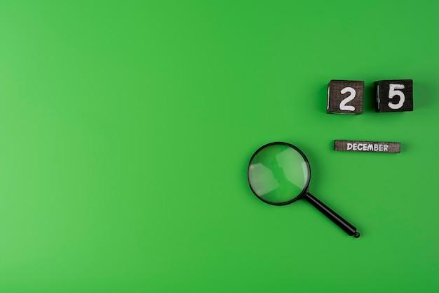 Lente d'ingrandimento lente d'ingrandimento su sfondo verde con spazio copia calendario in legno del 25 dicembre