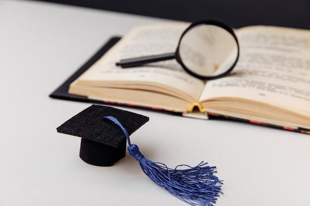 Lente d'ingrandimento sul libro aperto e cappuccio di graduazione sulla tavola bianca.