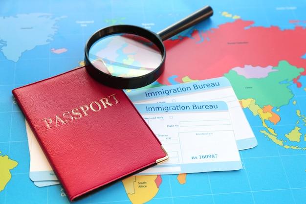 Lente d'ingrandimento e passaporto con carte di arrivo dell'ufficio immigrazione sulla mappa del mondo