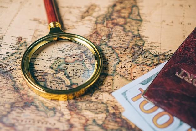 Lente d'ingrandimento e passaporto con soldi su una mappa del mondo vintage. vista dall'alto.