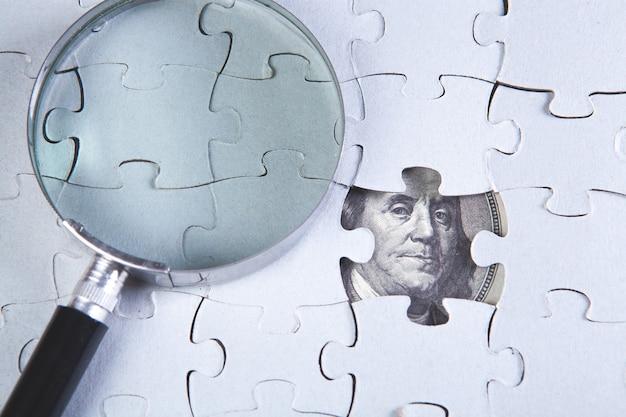 Una lente d'ingrandimento sui puzzle e una banconota da un dollaro