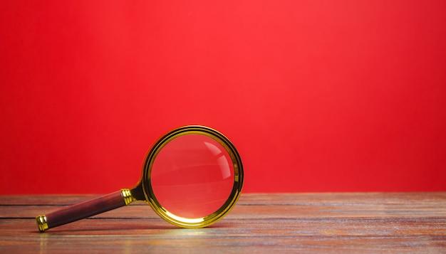 Lente d'ingrandimento su uno sfondo rosso. ricerca e analisi, analisi e studio.
