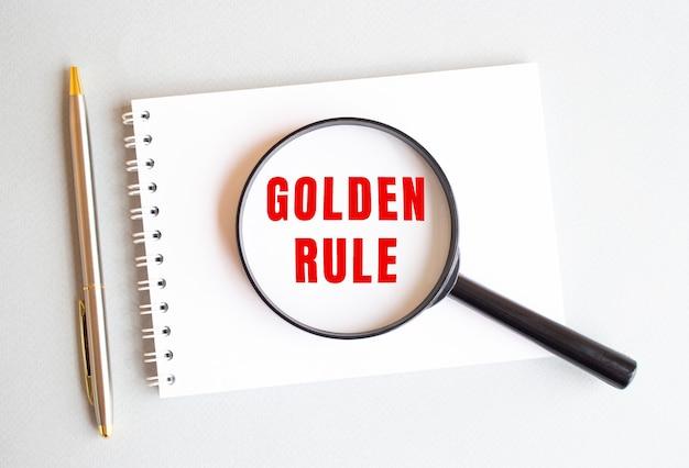 La lente d'ingrandimento si appoggia sul pad e mostra regola d'oro su una pagina bianca. c'è una penna accanto.