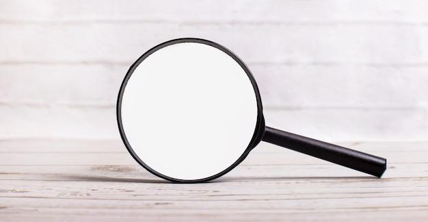 Una lente d'ingrandimento si erge verticalmente su uno sfondo chiaro con un posto dove inserire il testo. modello