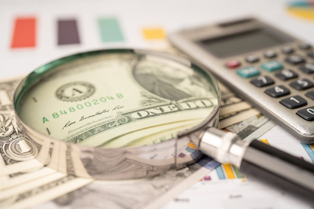 Lente d'ingrandimento e banconote in dollari usa su sfondo grafico, conto bancario, economia dei dati di ricerca analitica degli investimenti, commercio, concetto di società di affari.