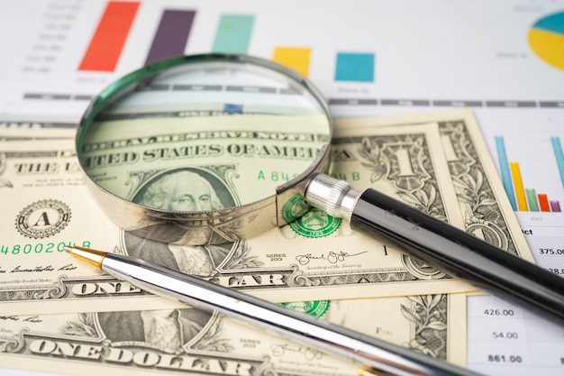 Lente d'ingrandimento e banconote in dollari usa su carta.