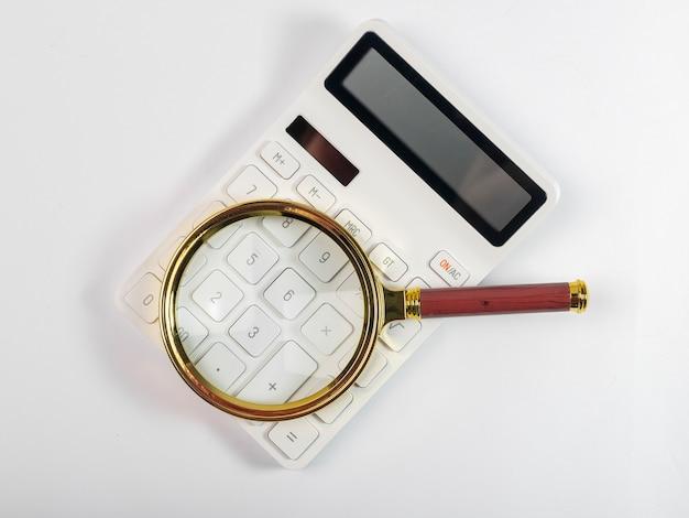 Lente d'ingrandimento sul calcolatore bianco, analisi e concetto di contabilità.