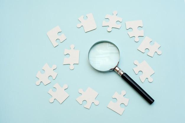 Lente d'ingrandimento e puzzle bianco su sfondo blu