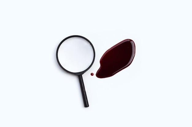 Lente d'ingrandimento con sangue su sfondo bianco.