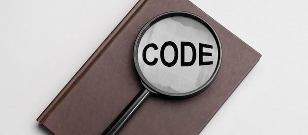Lente d'ingrandimento con segno di codice e taccuino marrone su sfondo grigio.