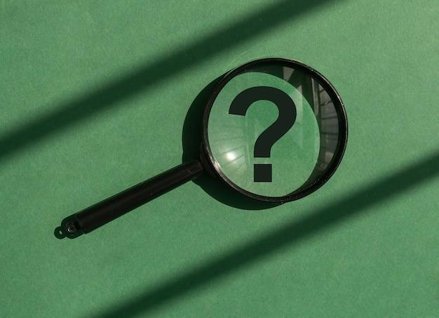 Lente di ingrandimento con punto interrogativo all'interno su sfondo verde concetto di studio di analisi che trova an...