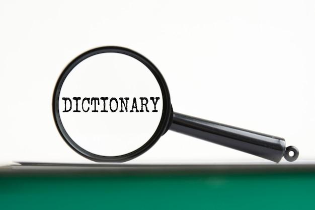 Lente d'ingrandimento con dizionario di testo su notebook con pagine verdi, sfondo bianco
