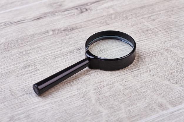 Lente d'ingrandimento su fondo di legno. lente con cornice nera. simbolo della narrativa poliziesca.