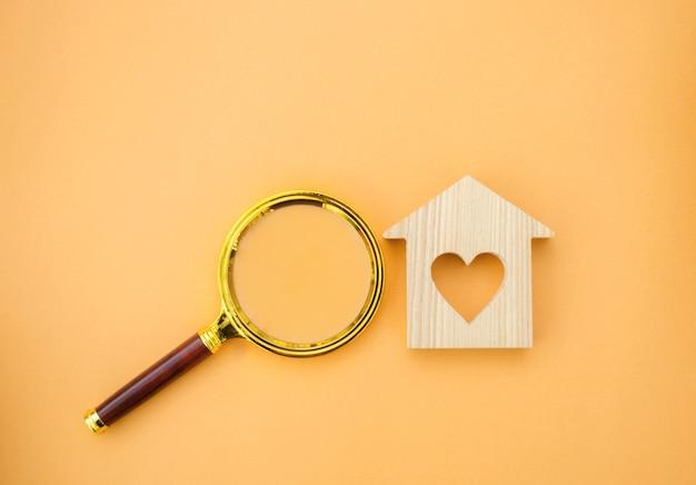 Lente d'ingrandimento e casa in legno concetto di ricerca della casa valutazione della casa valutazione della proprietà