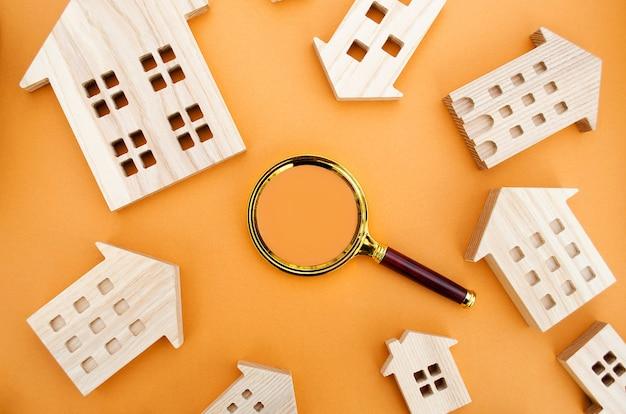 Lente d'ingrandimento e case in legno concetto di ricerca della casa valutazione della casa valutazione della proprietà