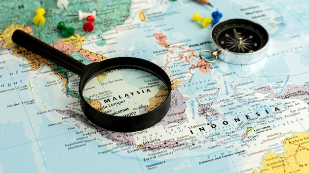 Lente d'ingrandimento sul fuoco selettivo della mappa di mondo alla mappa della malesia. - concetto economico e commerciale.