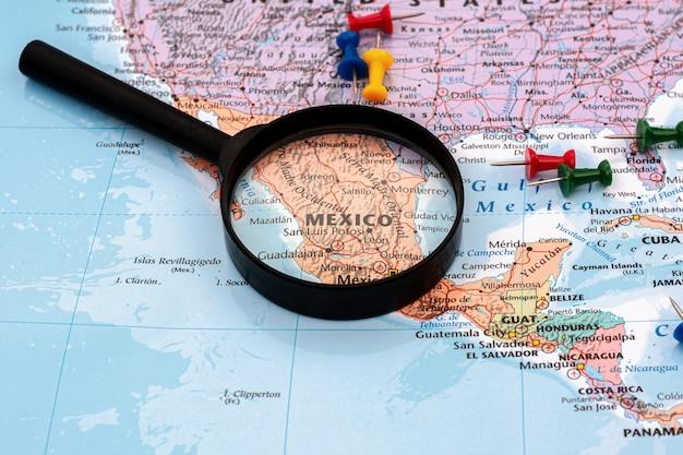 Lente d'ingrandimento sul fuoco selettivo della mappa di mondo alla mappa del messico. - concetto economico e commerciale.